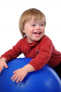 A boy with Down Syndrome on a ball